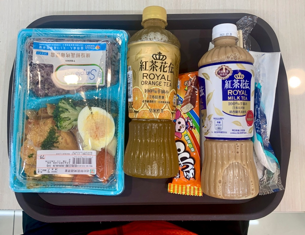 Food tray with drinks, candy bar, and rice meal