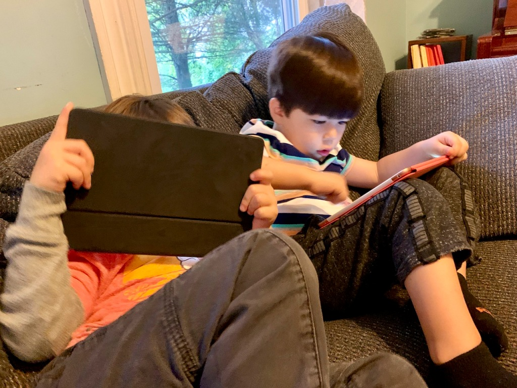Two kids giving iPads deep attention