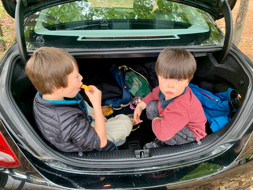 Two kids eating snacks in a car trunk
